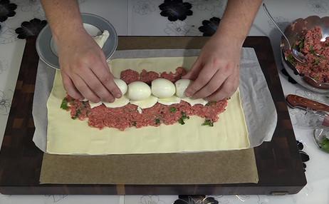 Он укладывает 4 сваренных вкрутую яйца прямо на подушку из фарша… Результат? Всем пирогам пирог!