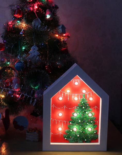 Из простой гирлянды и гофрокартона мастерица сделала симпатичный новогодний светильник-ночник...